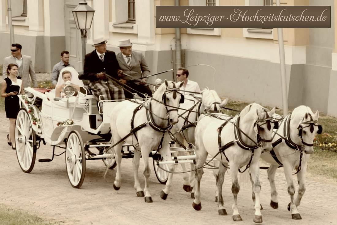 Brautpaar mit weißer Hochzeitskutsche